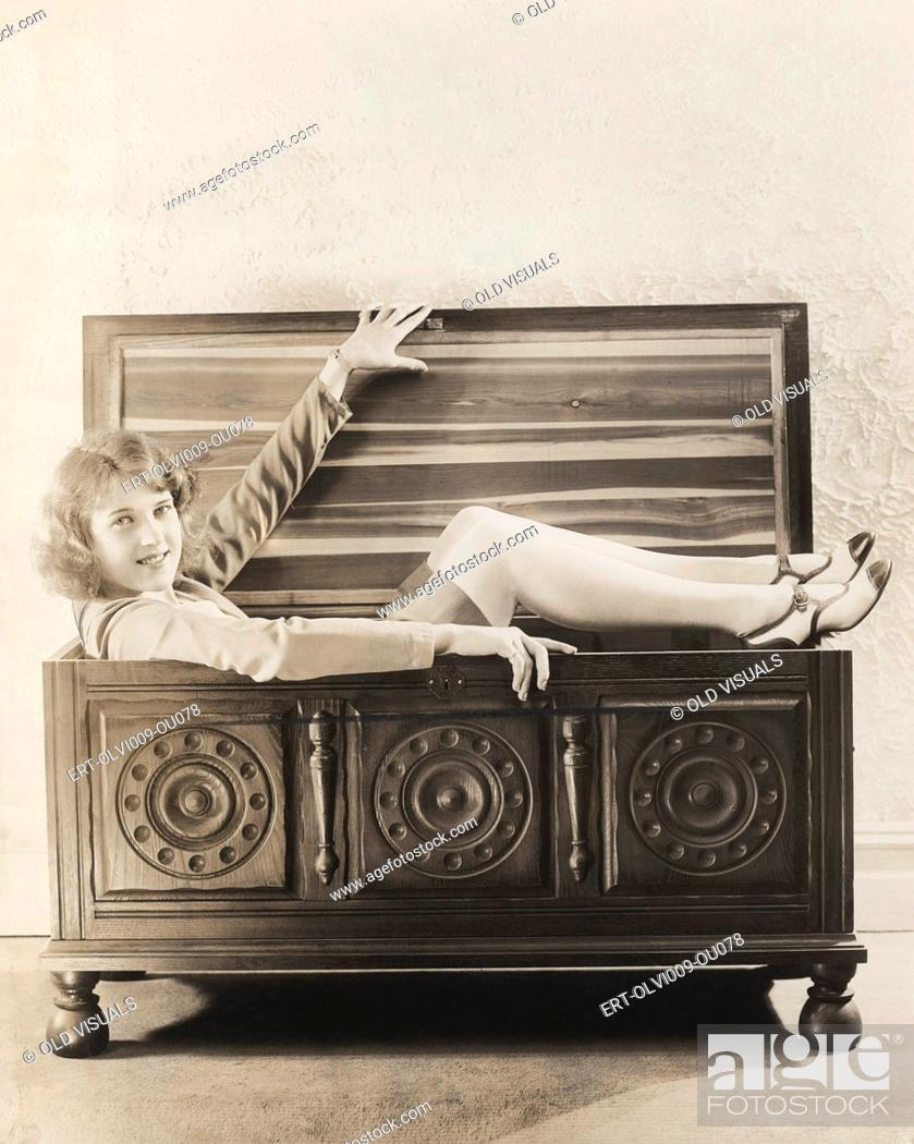 Stock Photo: Woman sitting in wooden chest.