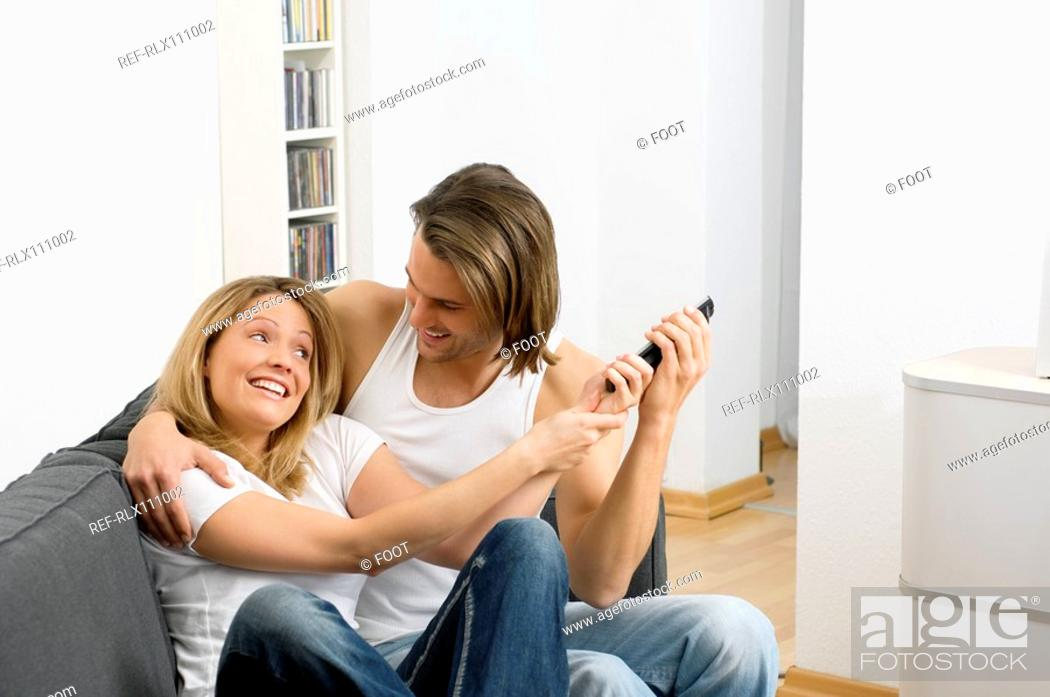 Stock Photo: Couple fighting over remote control.