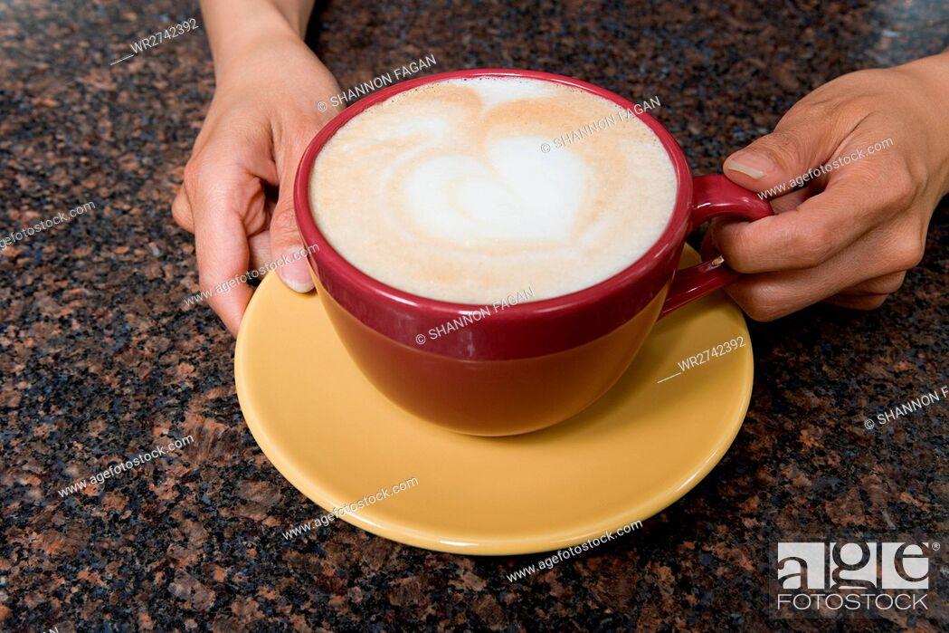 Stock Photo: Person holding cappuccino.