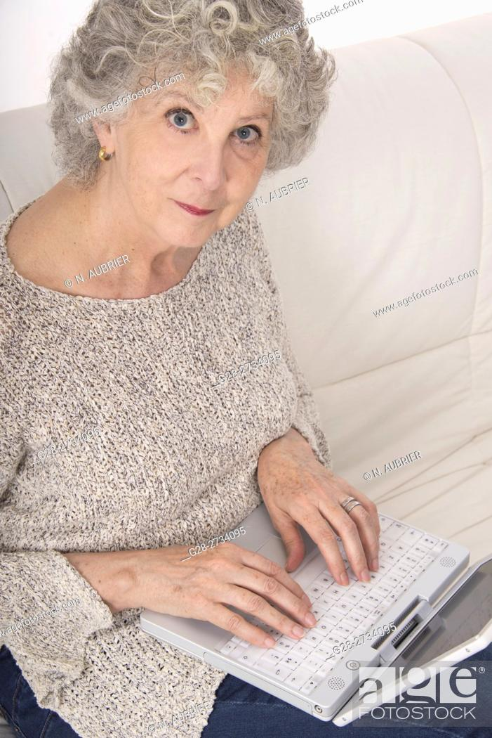 Stock Photo: Senior woman sitting on her sofa, Typing on the keyboard of her laptop computer.