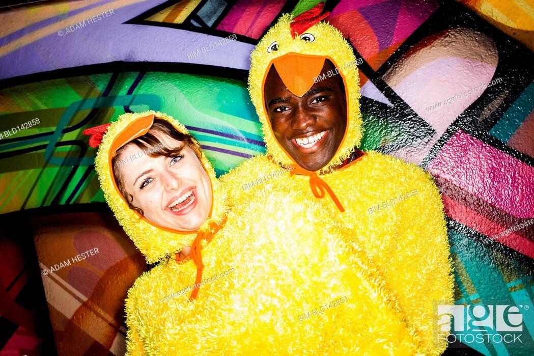 Imagen: Couple in chicken costumes smiling near graffiti wall.