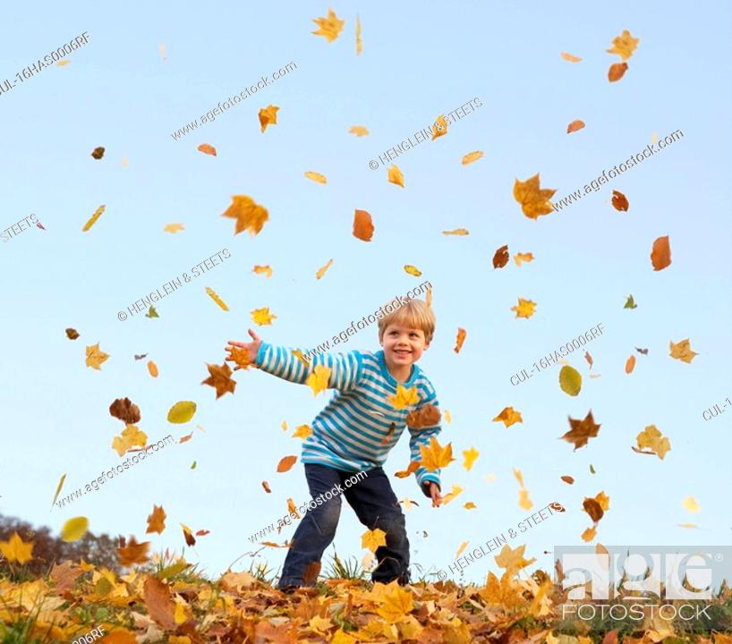 Stock Photo: boy throwing autumn leaves into the air.