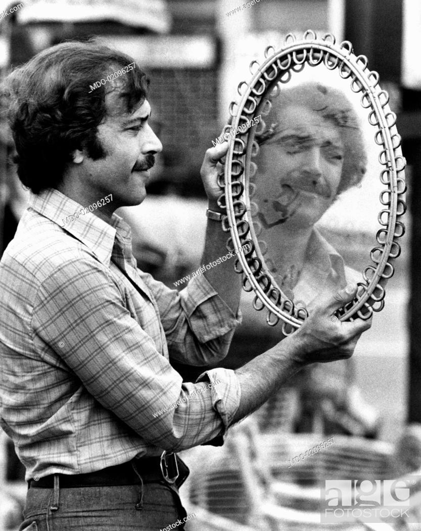 Imagen: Italian actor Orso Maria Guerrini looking his own face in a mirror at the flea market. Rome, 1970s.