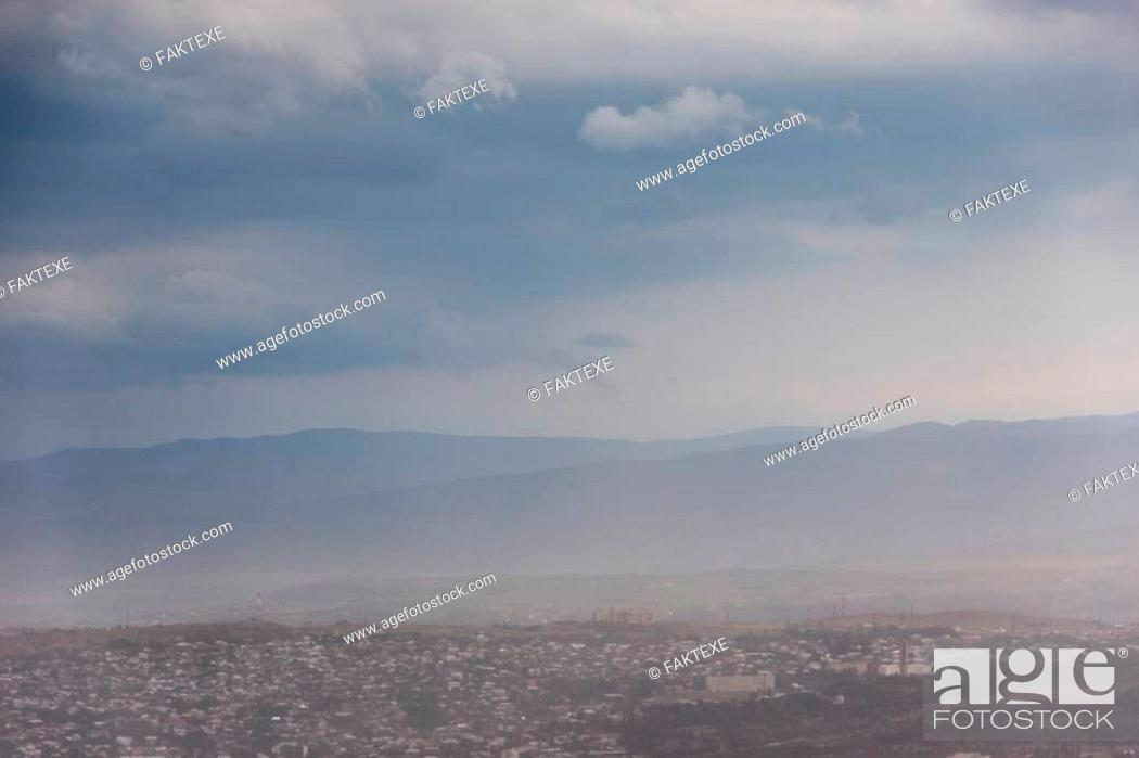 Stock Photo: A sandstorm during a thunderstorm over a town in the central Caucasus.