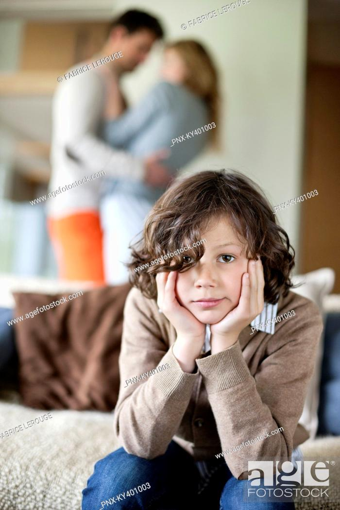Stock Photo: Boy sitting on a couch with his parents romancing in the background.