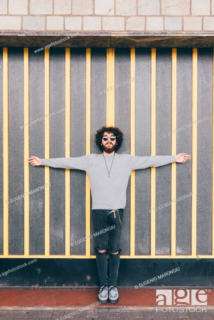 Stock Photo: Portrait of young man, arms outstretched, in urban environment.