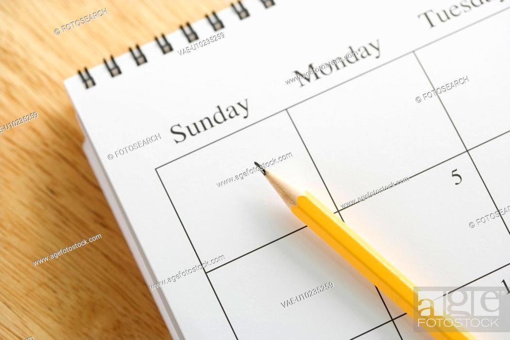 Stock Photo: Pencil on top of a spiral bound calendar.