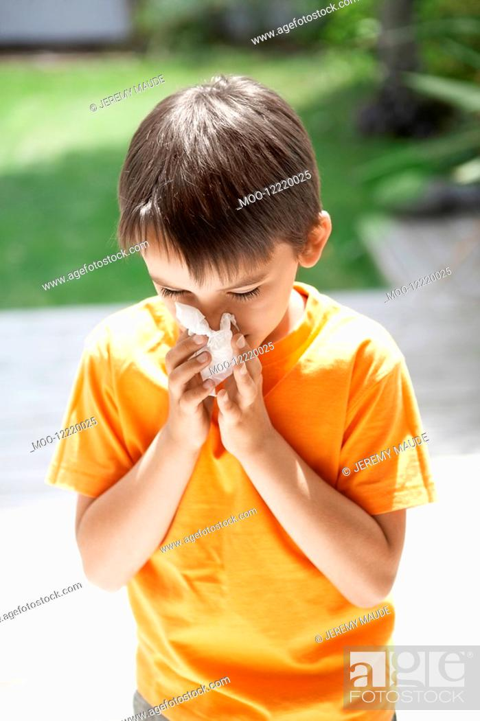 Stock Photo: Little Boy Blowing His Nose in back yard.