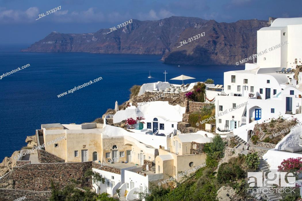 Stock Photo: Traditional Greek flag with domed Orthodox Church overlooking the Aegean Sea in Oia Santorini Greece.