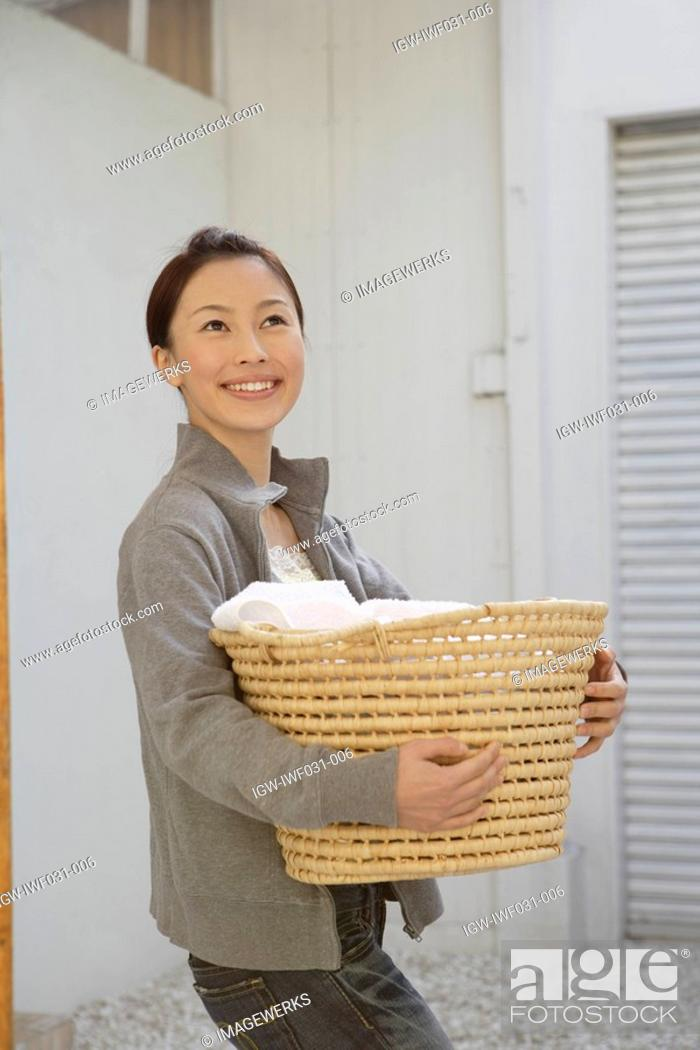 Stock Photo: Side view of a young woman holding a basket.