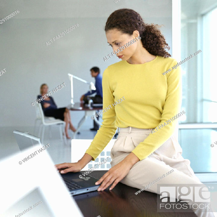 Stock Photo: Woman sitting on edge of desk in office.