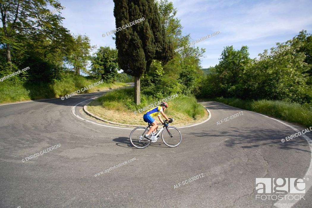 Stock Photo: Cyclist cornering on switchback road, side view.
