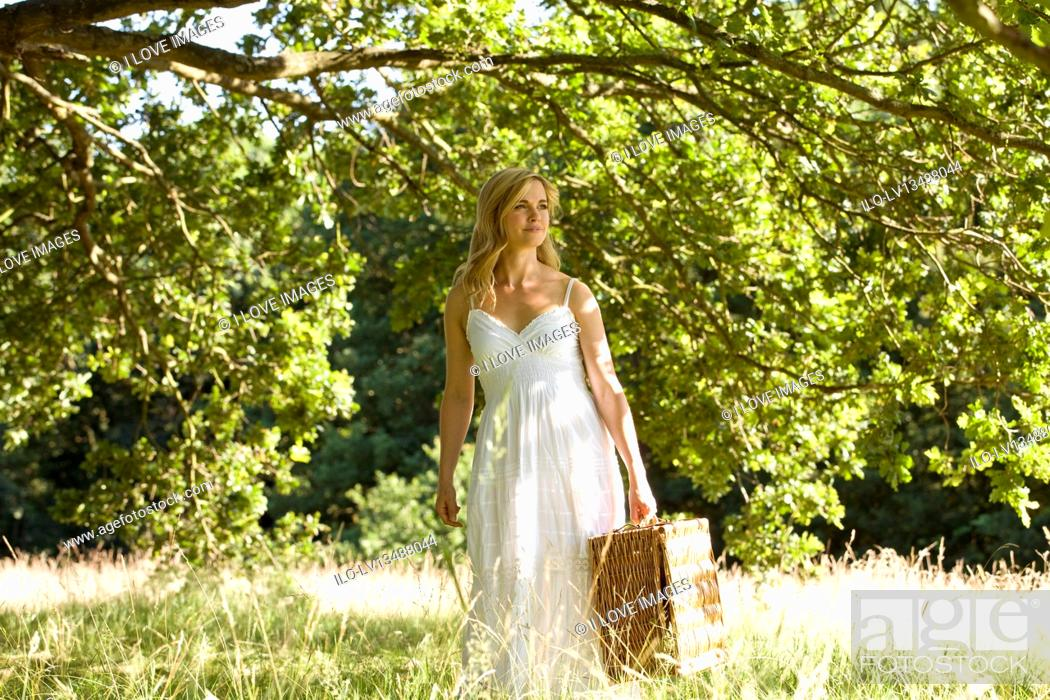 Stock Photo: A young woman carrying a picnic basket.