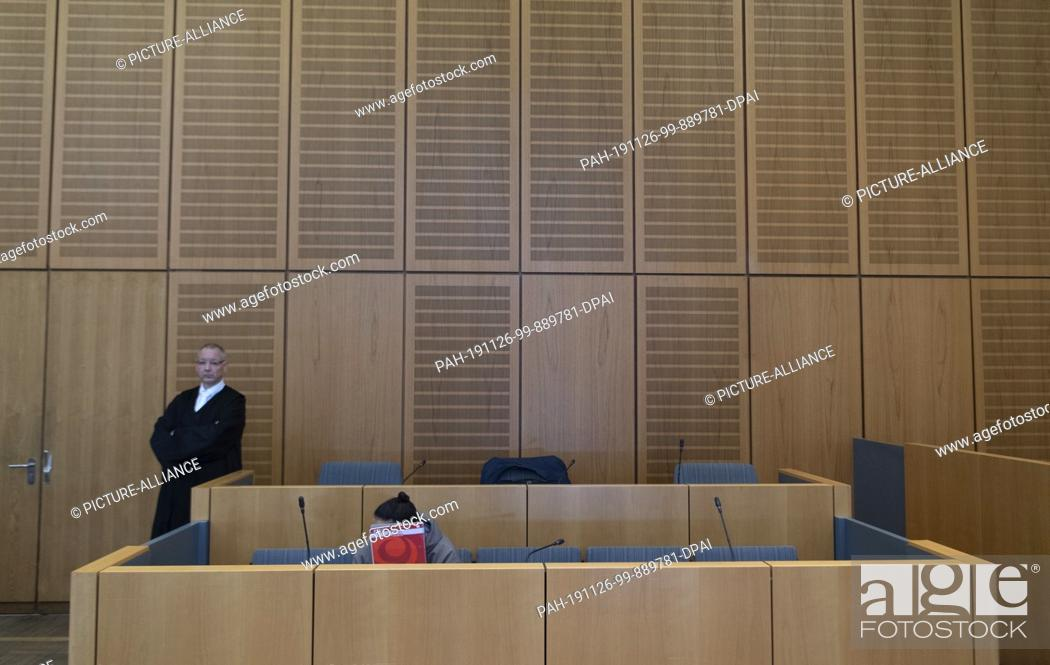 Stock Photo: 26 November 2019, Rhineland-Palatinate, Mainz: With a writing pad, the 28-year-old defendant covers his face in the dock in the courtroom of the regional court.
