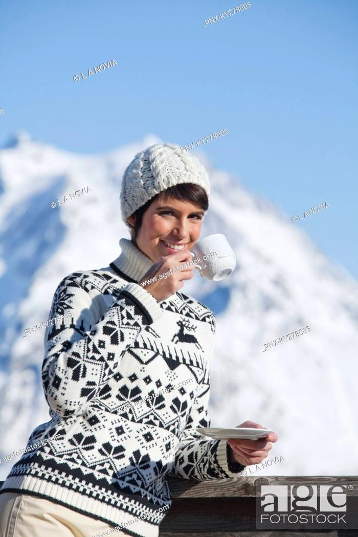 Stock Photo: Young woman drinking coffee, mountains in background.
