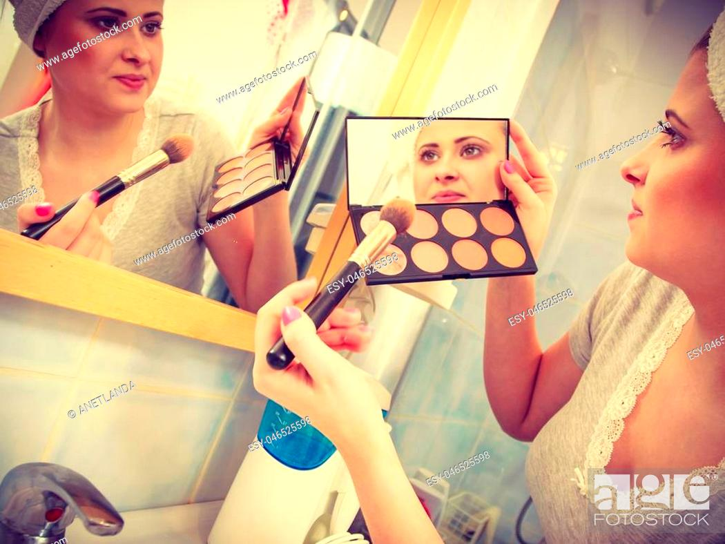 Stock Photo: Contouring face kit, visage and make up concept. Woman in bathroom applying contour bronzer on brush.