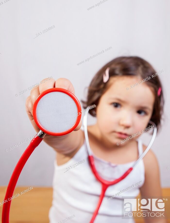 Imagen: Little girl showing and playing with a stethoscope. Isolated over white background.