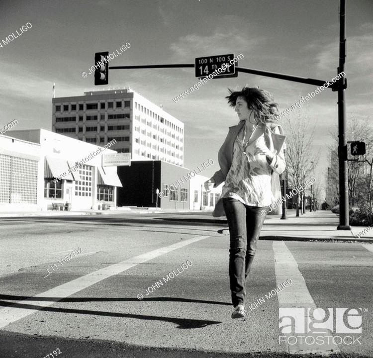 Stock Photo: Young woman, running across empty downtown street.