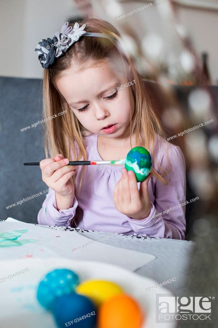 Stock Photo: A happy little child coloring easter eggs. Cozy home atmosphere. Easter.