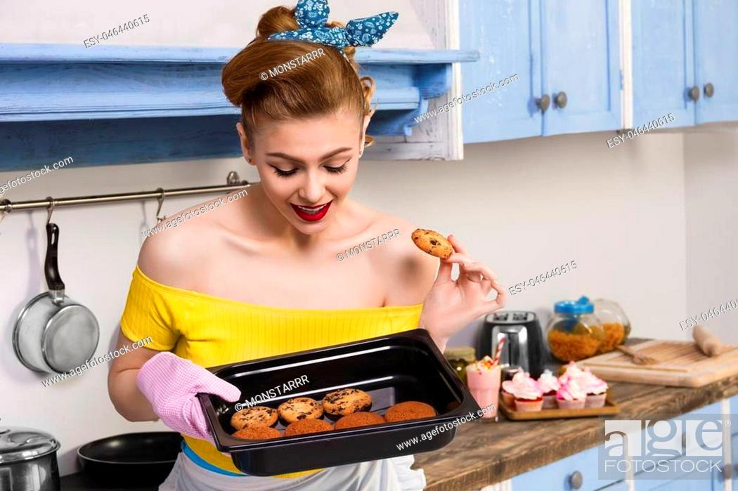 Imagen: Retro pin up girl woman female / housewife wearing colorful top holding tray with home cooked cookies standing in the kitchen with blue cabinets and utensils.