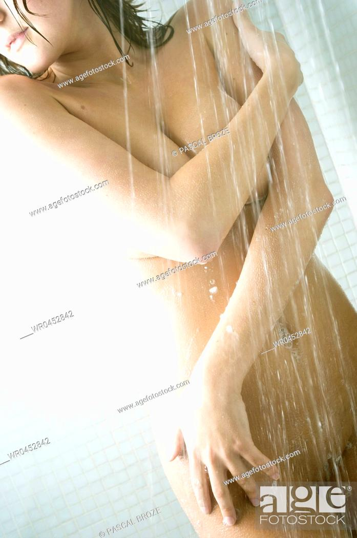 Stock Photo: Naked young woman taking a shower in the bathroom.