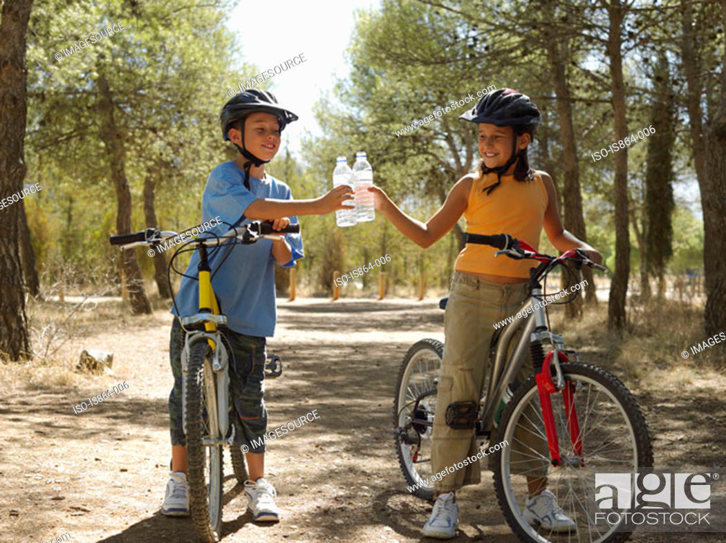 Stock Photo: Boy and girl on bikes with water bottles.