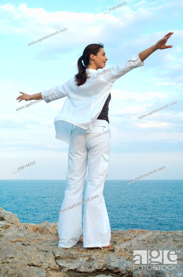 Stock Photo: Woman on a rock at the sea.