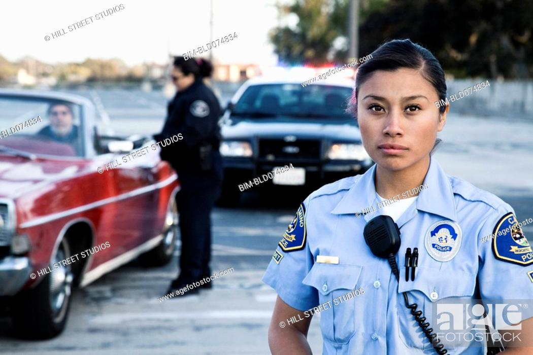 Stock Photo: Policewomen pulling over man in convertible.