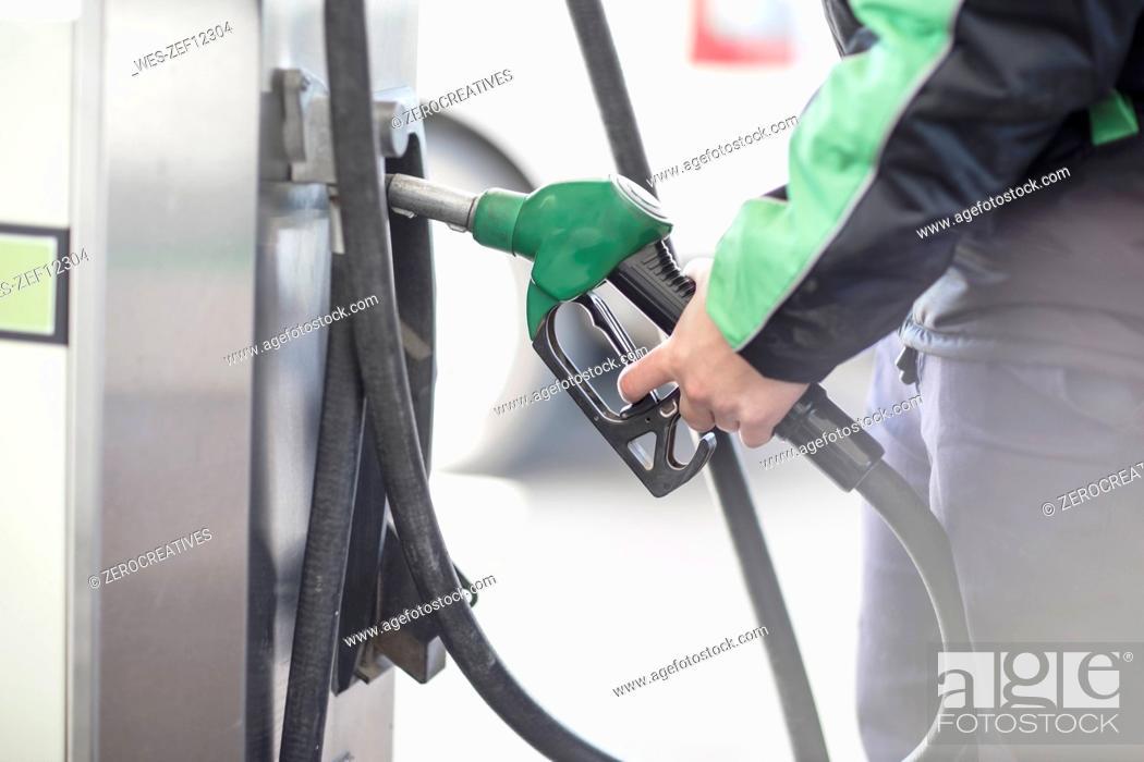 Stock Photo: Petrol attendant holding petrol pump.