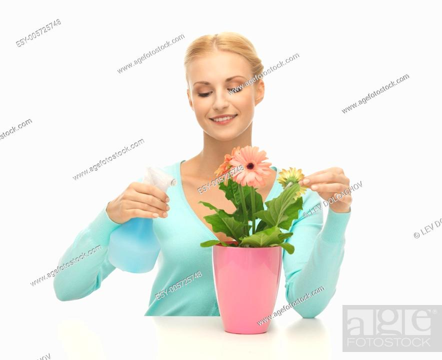 Stock Photo: young woman holding pot with flower and spray bottle.