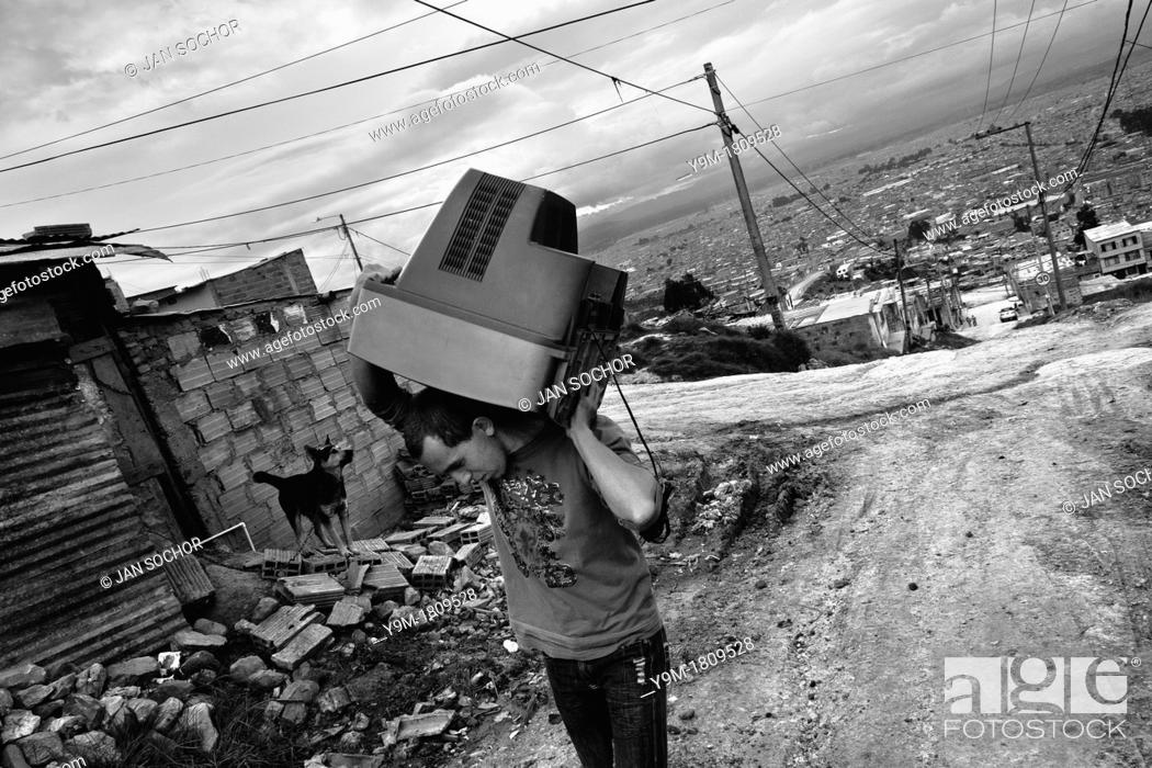Stock Photo: A displaced man carries a used TV on his shoulder in the slum of Ciudad Bolívar, Bogota, Colombia, 31 May 2010  With nearly fifty years of armed conflict.