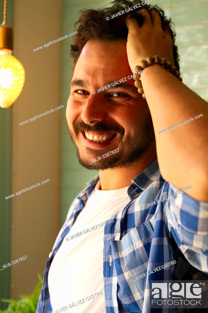Stock Photo: young man posing with natural light from window with carefree pose smiling.