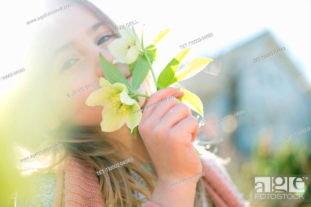 Photo de stock: Portrait of girl smelling yellow flowers.