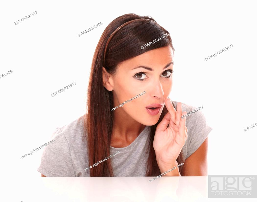 Stock Photo: Attractive brunette who is whispering a secret while looking at camera on white background.