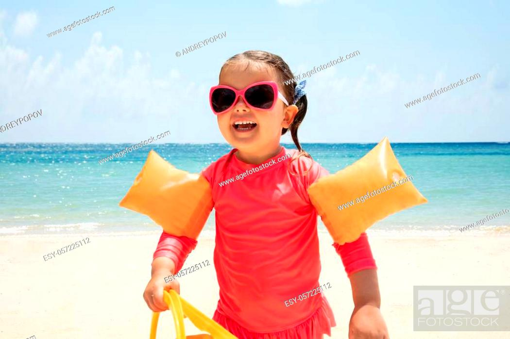 Stock Photo: Portrait Of A Happy Toddler Girl Holding Plastic Toys In Hand Walking On Sandy Beach.