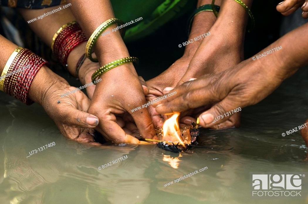 Stock Photo: Women perform a puja ceremony at the Ganges river.