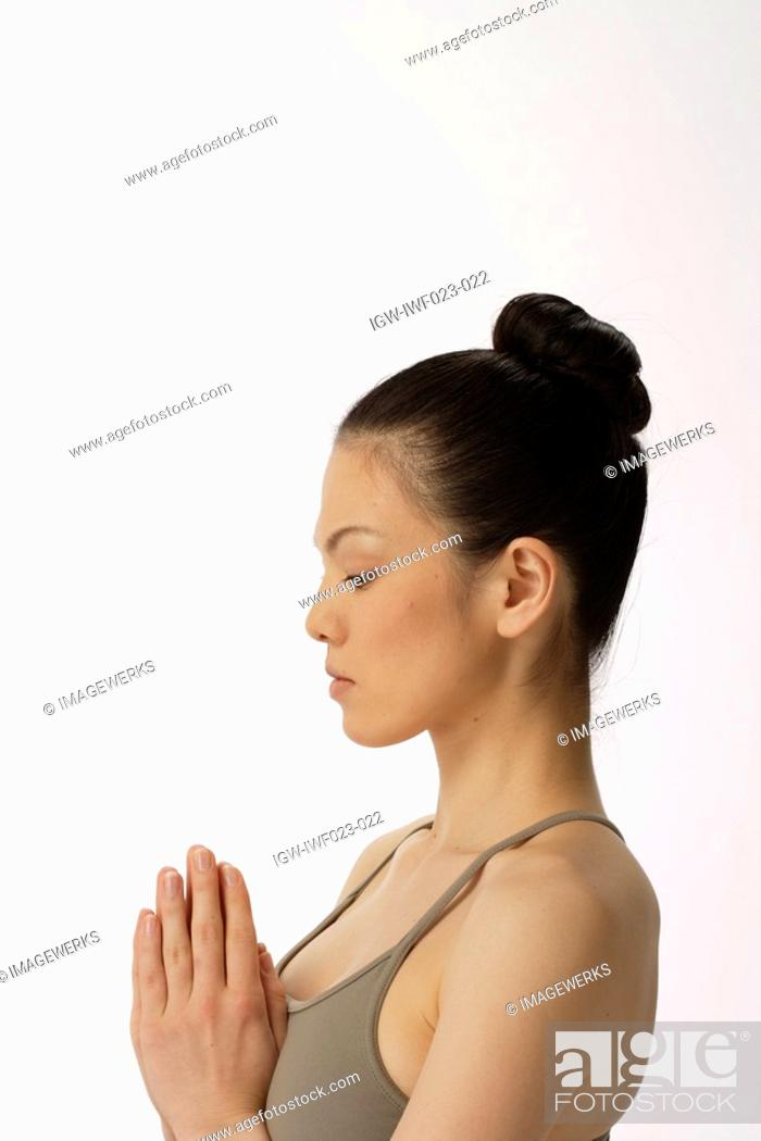 Stock Photo: Side view of a young woman meditating.