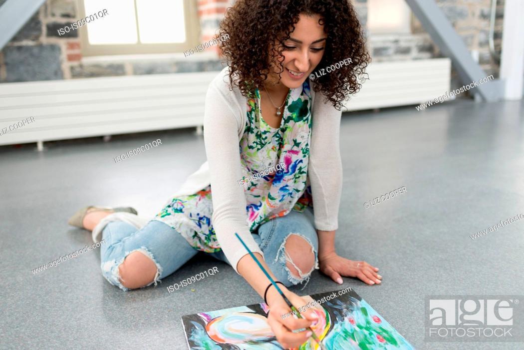 Imagen: Young female painter painting canvas on studio floor.