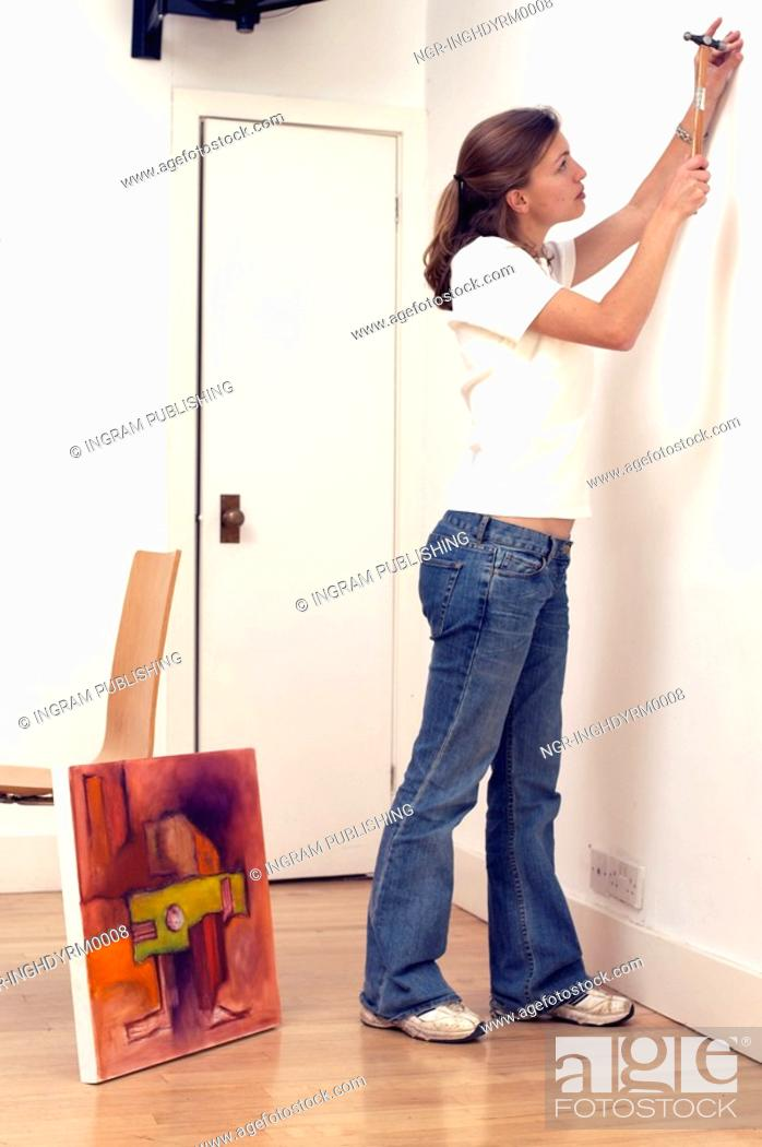 Stock Photo: Side profile of a young woman hammering a nail into a wall.