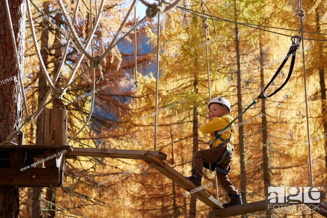Stock Photo: Young boy climbing in forest, attached to high line rope.