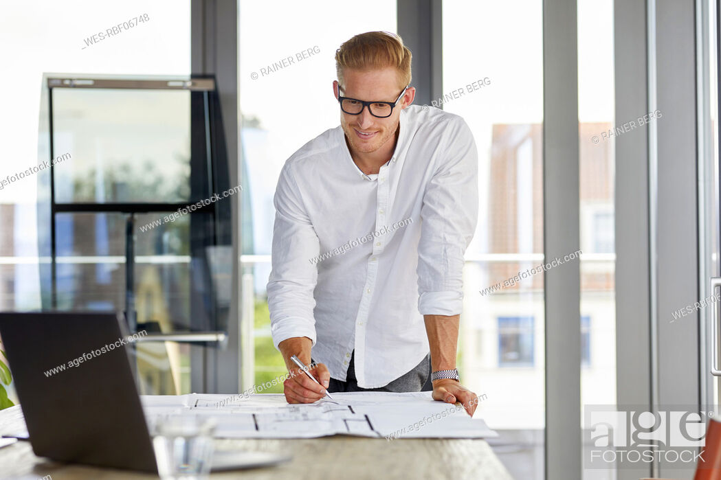Stock Photo: Smiling young man working on blueprint on desk in office.