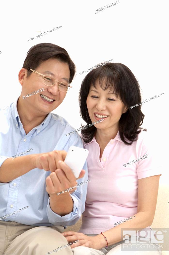Stock Photo: Couple, Couple looking at the mobile phone together and smiling happily.