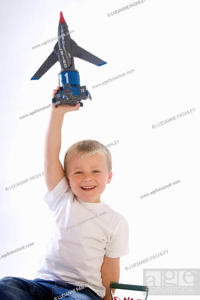 Stock Photo: 5 Year old boy holding a toy aeroplane up in the air smiling into camera.