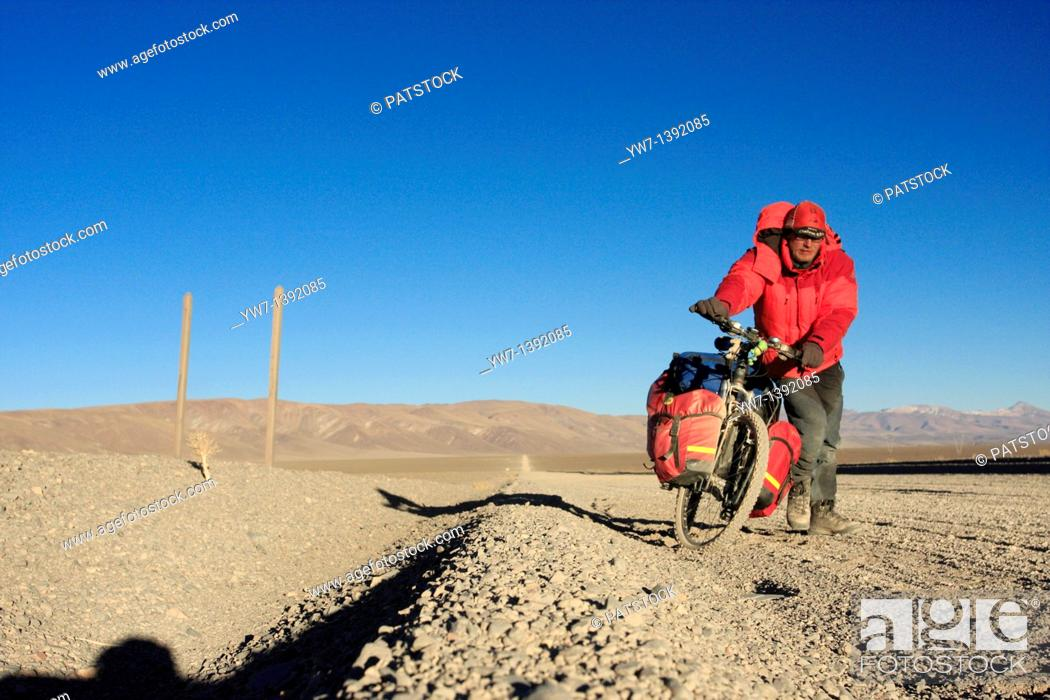 Stock Photo: A biker in the Andes, Salta district, to the west of San Antonio de los Cobres, Argentina, on the way to the border with Chile.