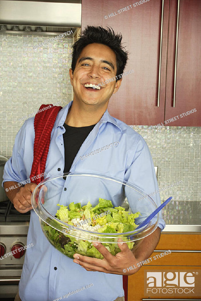 Stock Photo: Man in kitchen holding salad serving bowl.
