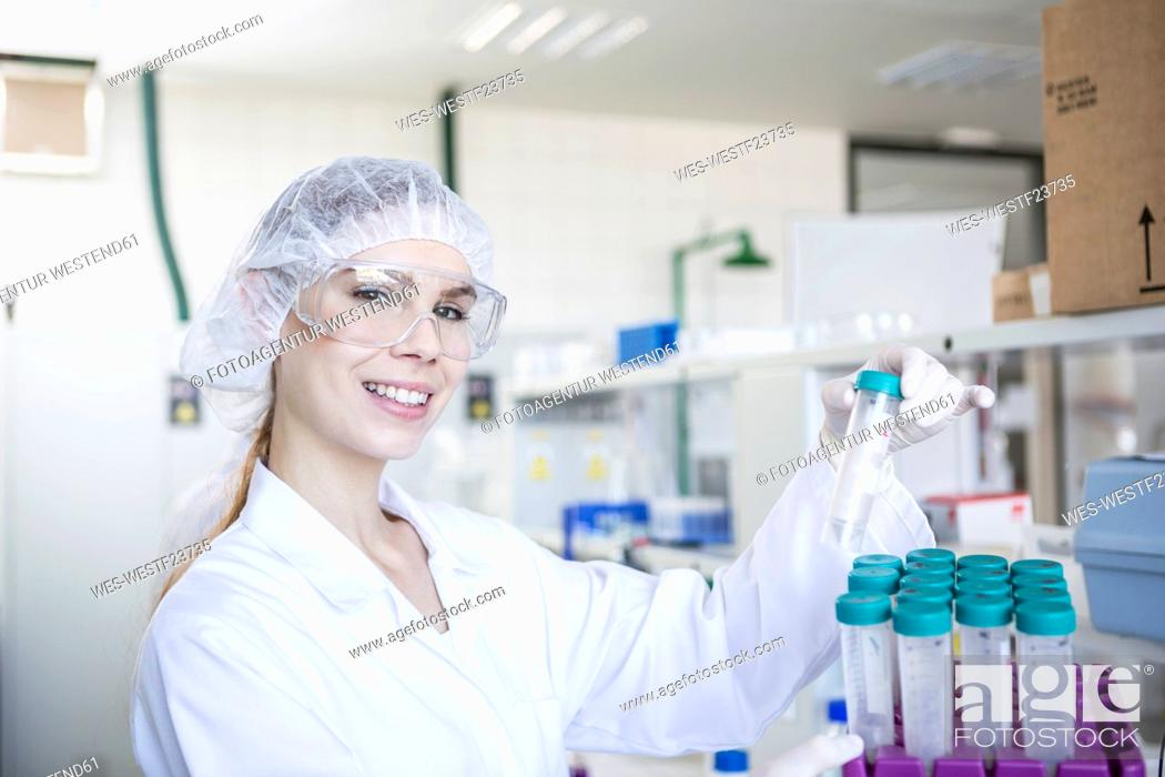 Imagen: Portrait of smiling scientist in lab holding test tube.