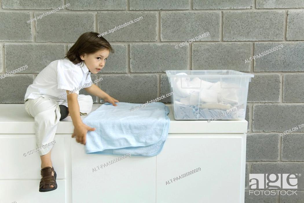 Stock Photo: Little boy folding laundry, sitting on counter.