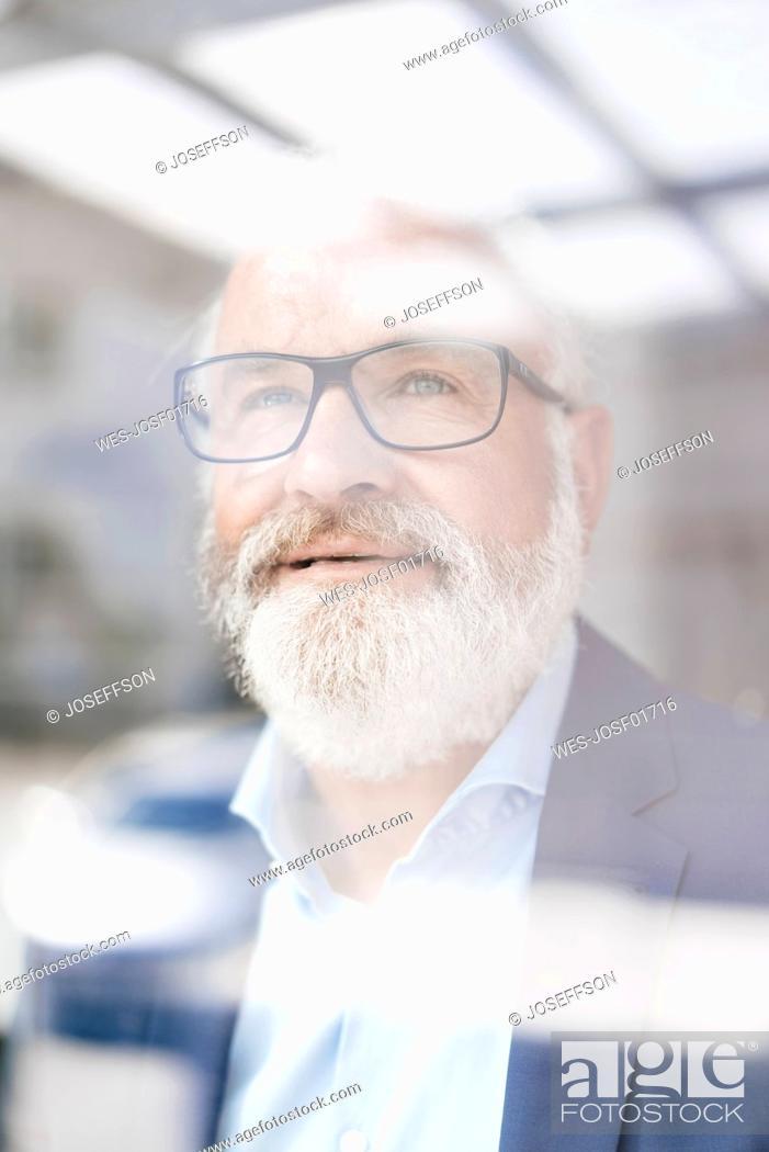 Stock Photo: Portrait of mature man behind windowpane.