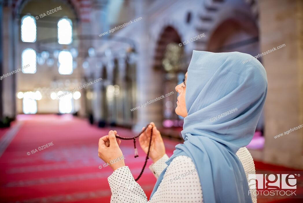 Stock Photo: Muslim woman in headscarf and hijab prays with her hands up in air while holding rosary in mosque. Religion praying concept.