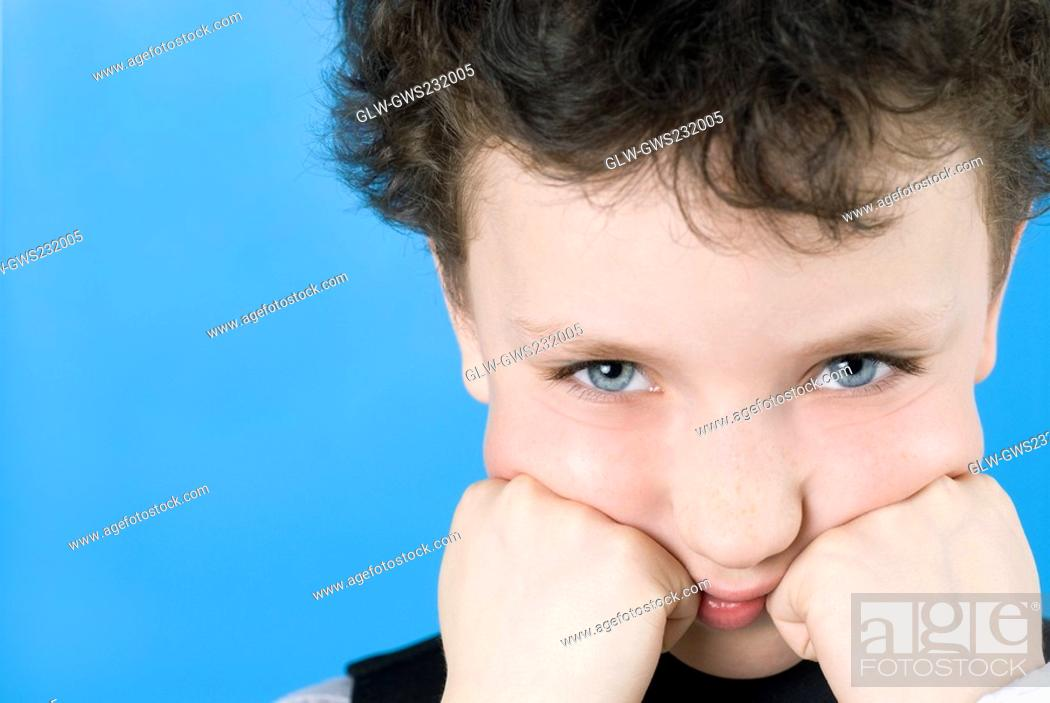 Stock Photo: Portrait of a boy with his hands on his cheeks.